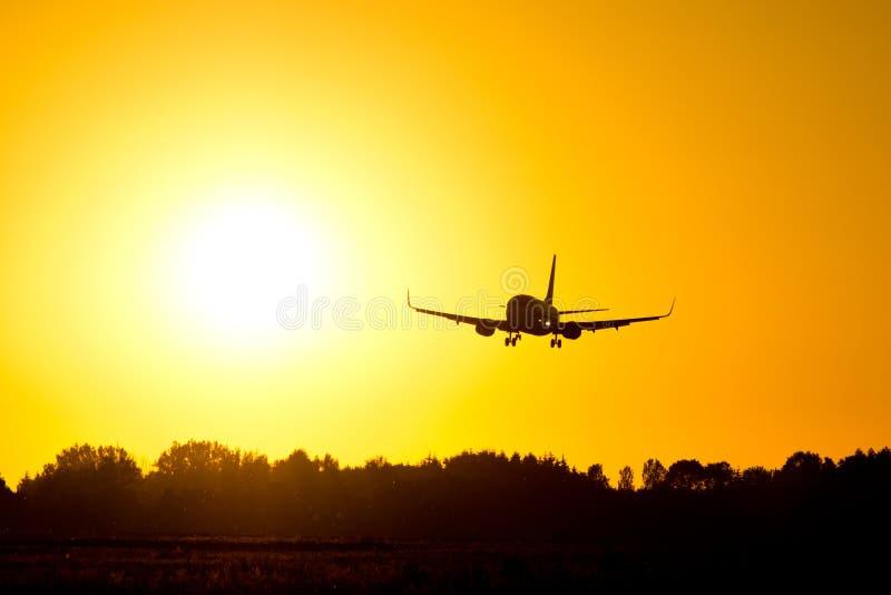 Atterraggio di aeroplano durante il tramonto fotografia stock