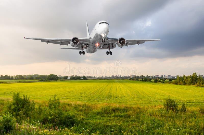 Atterraggio di approccio dell'aeroplano dell'aeroplano sopra il campo di erba verde all'aeroporto immagini stock
