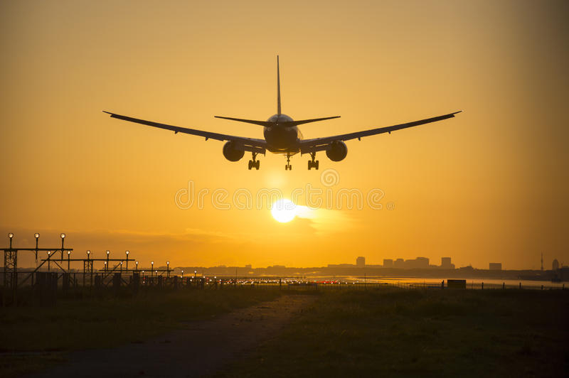 Atterrissage d'avion pendant le crépuscule photographie stock