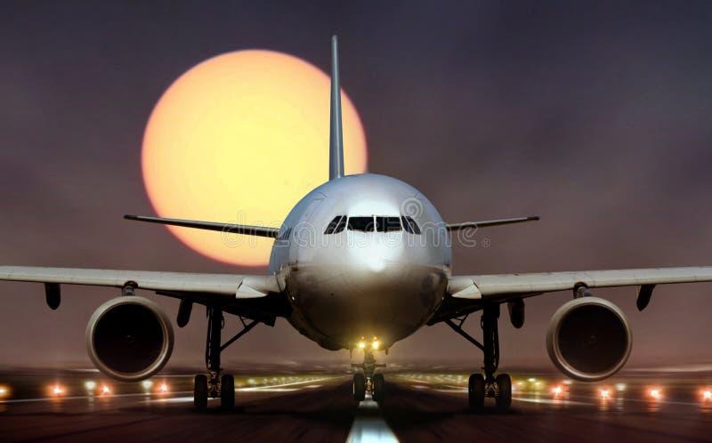 Atterrissage d'avion sur la piste pendant le coucher du soleil image stock