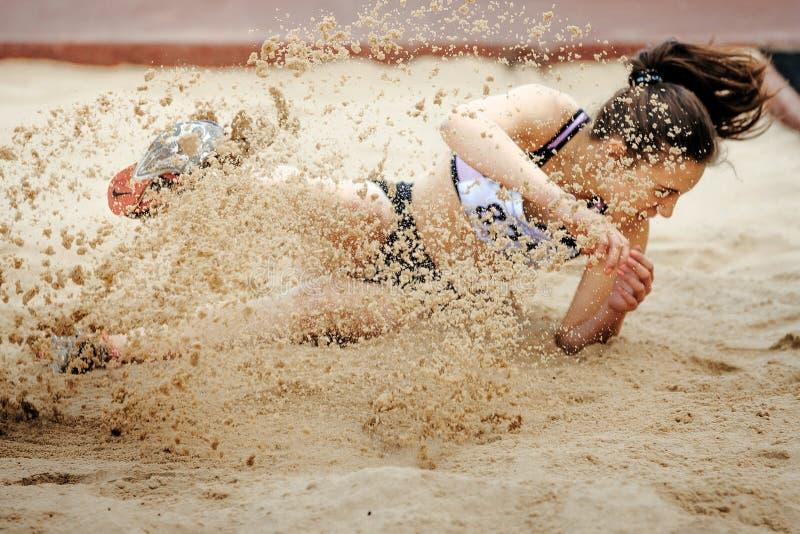 Atterrissage de pullover de femmes dans le long saut de sable photo libre de droits