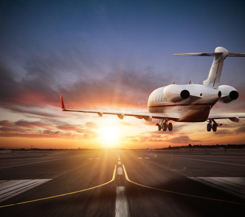 Atterrissage privé d'avion à réaction sur la piste dans la belle lumière de coucher du soleil images stock