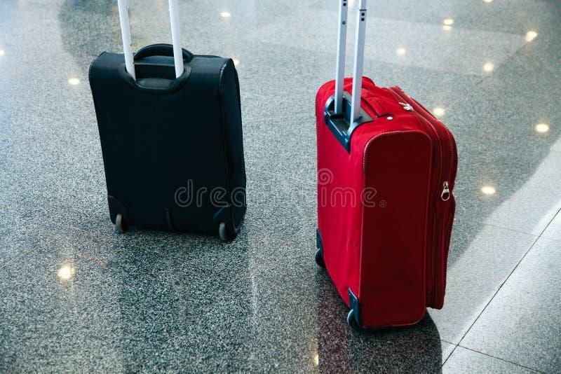 Attesa del blak di rosso blu della borsa dell'aeroporto dei bagagli del bagaglio del passeggero immagini stock libere da diritti