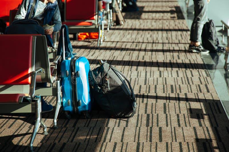Attesa del blak di rosso blu della borsa dell'aeroporto dei bagagli del bagaglio del passeggero immagine stock