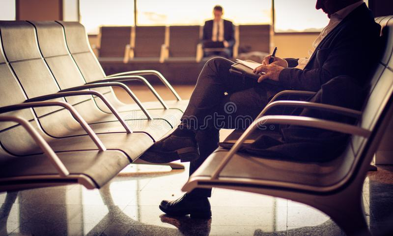 Attesa del suo volo Uomo all'aeroporto immagine stock libera da diritti