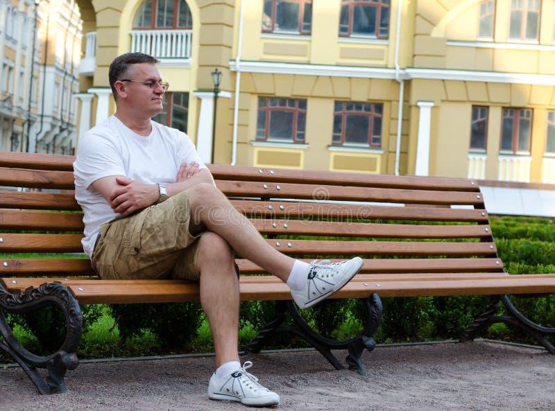 Attesa di seduta dell'uomo su un banco urbano fotografia stock