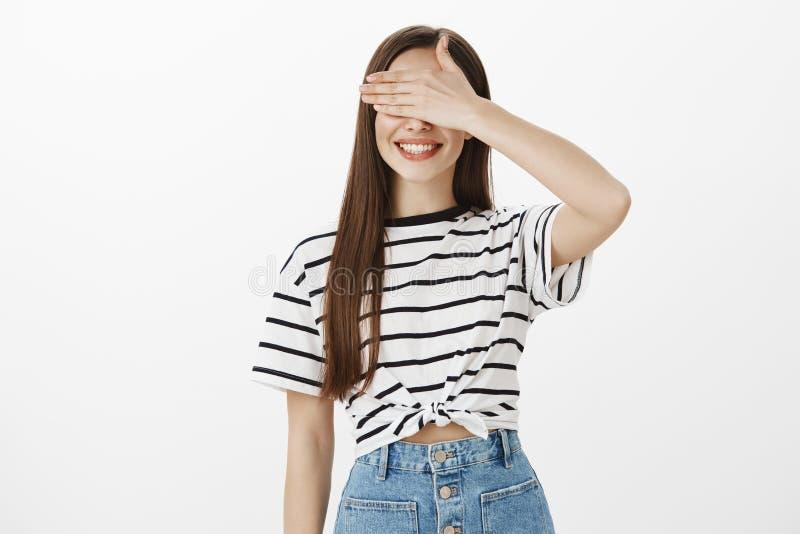 Attesa per vedere che cosa i suoi cari amici hanno preparato Colpo dello studio della donna intrigante attraente in maglietta a s fotografia stock