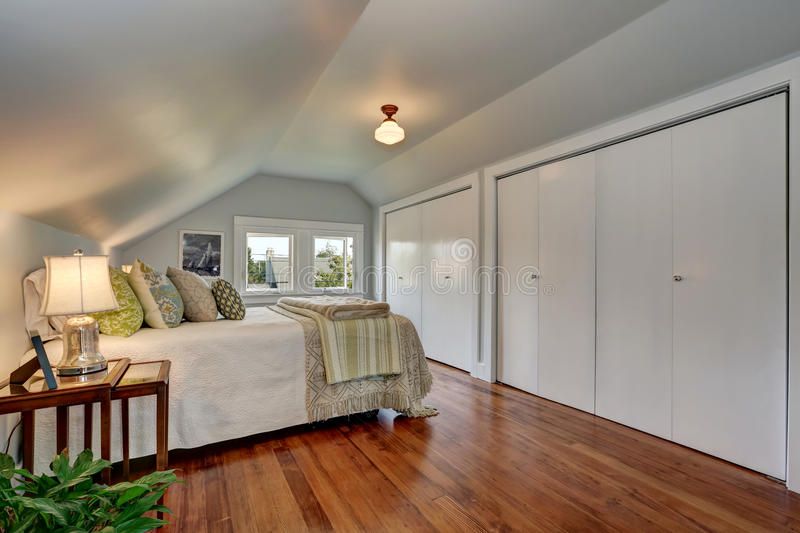 Attic bedroom interior with vaulted ceiling and hardwood floor. royalty free stock photography