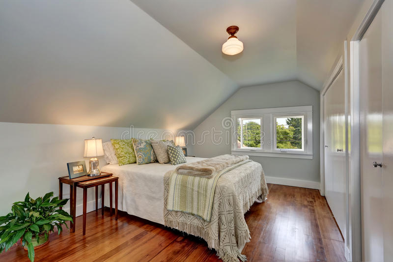 Attic bedroom interior with vaulted ceiling and hardwood floor. royalty free stock images