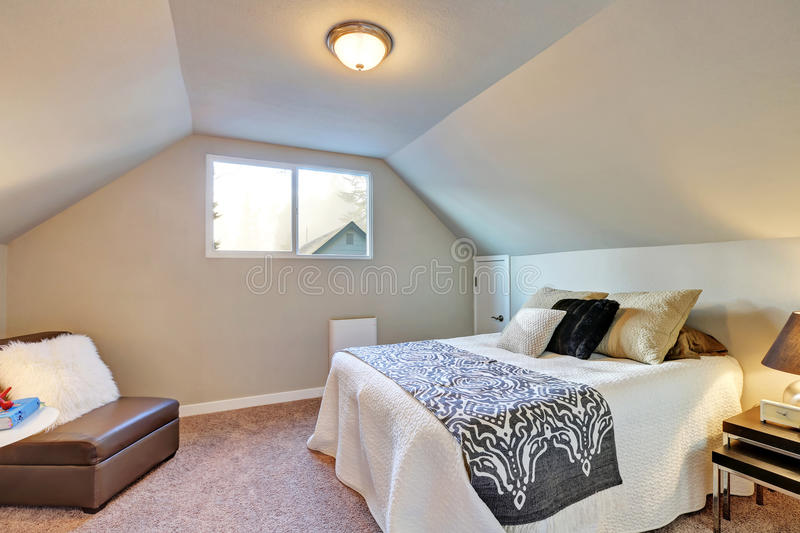 Attic bedroom with large bed and carpet floor. royalty free stock images