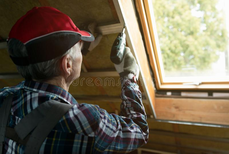 Attic insulation and renovation. Man fixing metal frame using an electric screwdriver on ceiling covered with rock wool stock photos