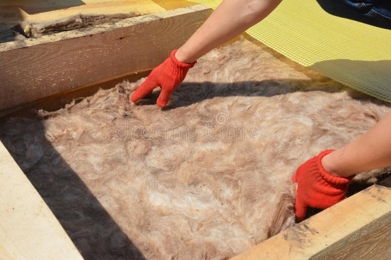Attic Insulation. Roofer Hands Installing House Roof Thermal Insuation with Mineral Wool royalty free stock images