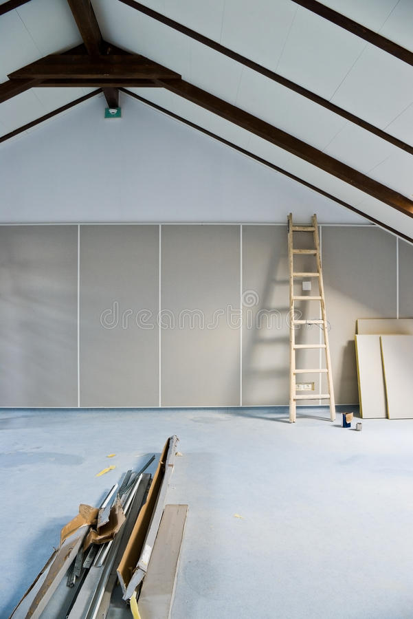 Attic renovation. Step ladder and construction materials in empty attic room royalty free stock photography
