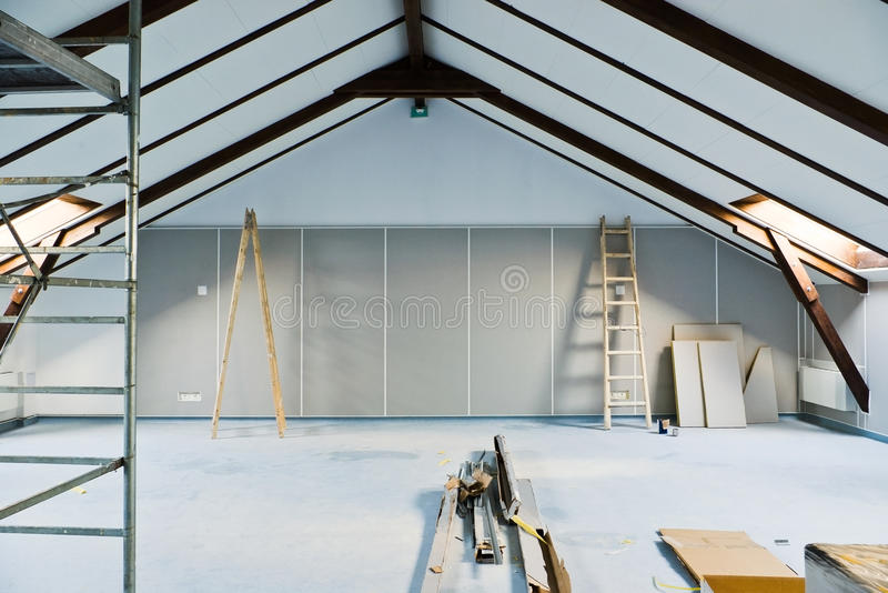 Attic renovations. With ladder and gray walls royalty free stock image