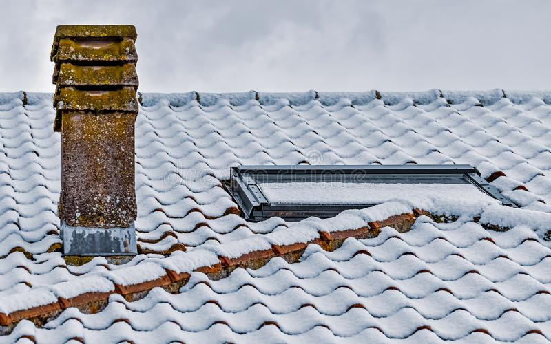 Attic window and chimney covered by snow stock photography