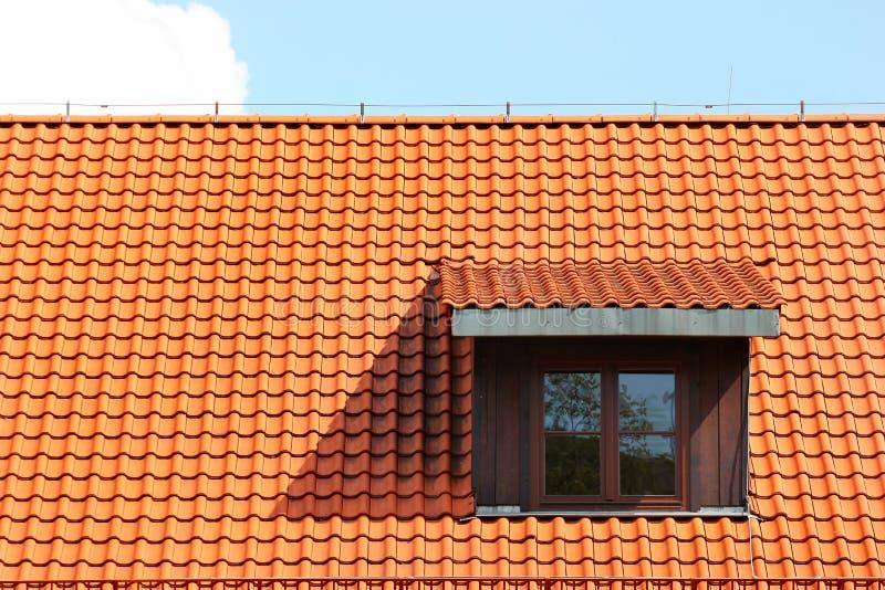 Attic window in orange tiled roof royalty free stock photo