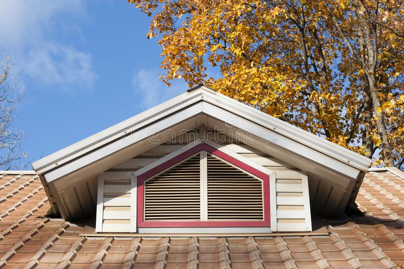 Attic window with wooden shutters on the tiled roof. Architecture detail. Autumn season royalty free stock photography