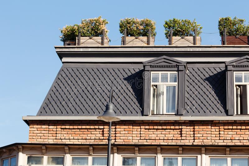 Attic windows on the building roof with flower boxes at sunny day stock images