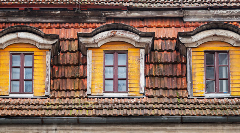 Attic windows of old wooden house stock image