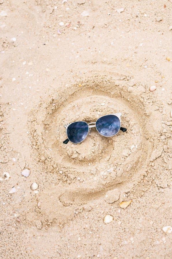 Attingendo sabbia, sorriso strappato sotto forma di spirale, in occhiali da sole fotografie stock libere da diritti