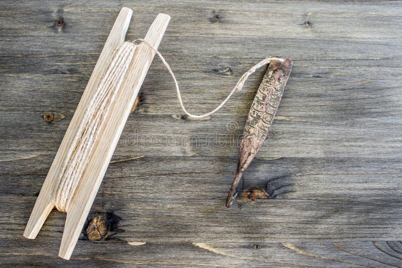 Attirail antique pour les poissons prédateurs instantané vertical Fileur et bobine forgés de cuivre avec la corde sur le fond en  image stock