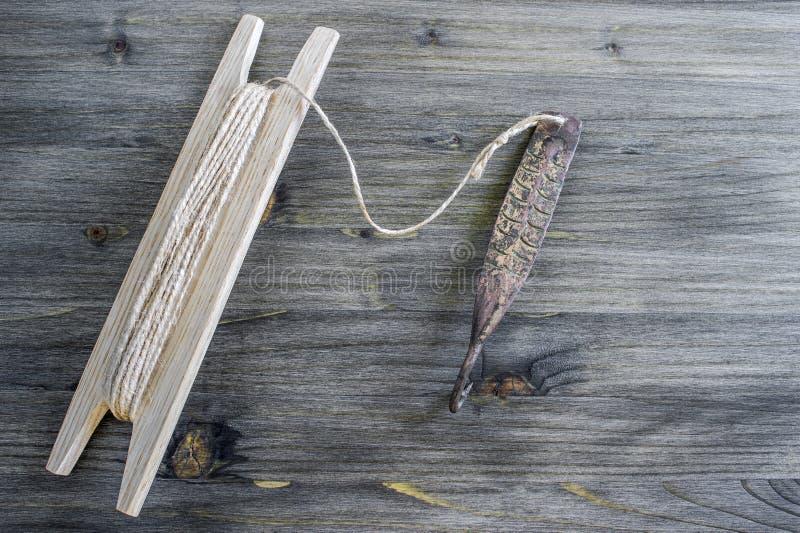 Attirail antique pour les poissons prédateurs instantané vertical Fileur et bobine forgés de cuivre avec la corde sur le fond en  photo libre de droits