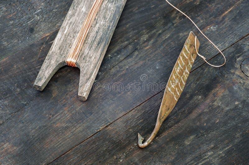 Attirail antique pour les poissons prédateurs instantané vertical Fileur et bobine forgés de cuivre avec la corde sur le fond rus photos stock