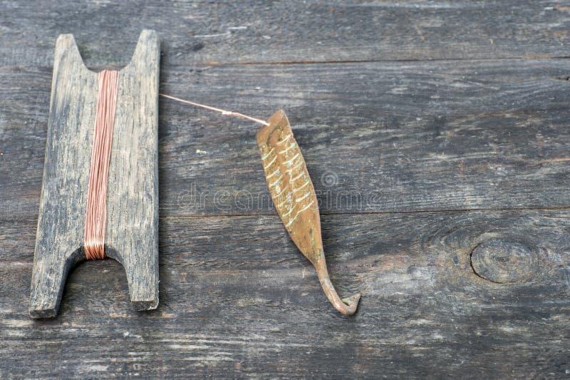 Attirail antique pour les poissons prédateurs instantané vertical Fileur et bobine forgés de cuivre avec la corde sur le fond rus images libres de droits