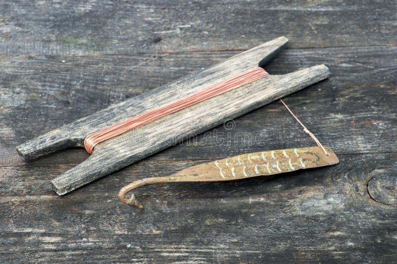 Attirail antique pour les poissons prédateurs instantané vertical Fileur et bobine forgés de cuivre avec la corde sur le fond rus image libre de droits