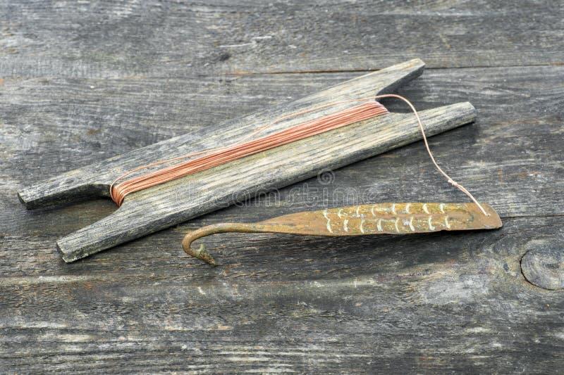 Attirail antique pour les poissons prédateurs instantané vertical Fileur et bobine forgés de cuivre avec la corde sur le fond rus photo stock