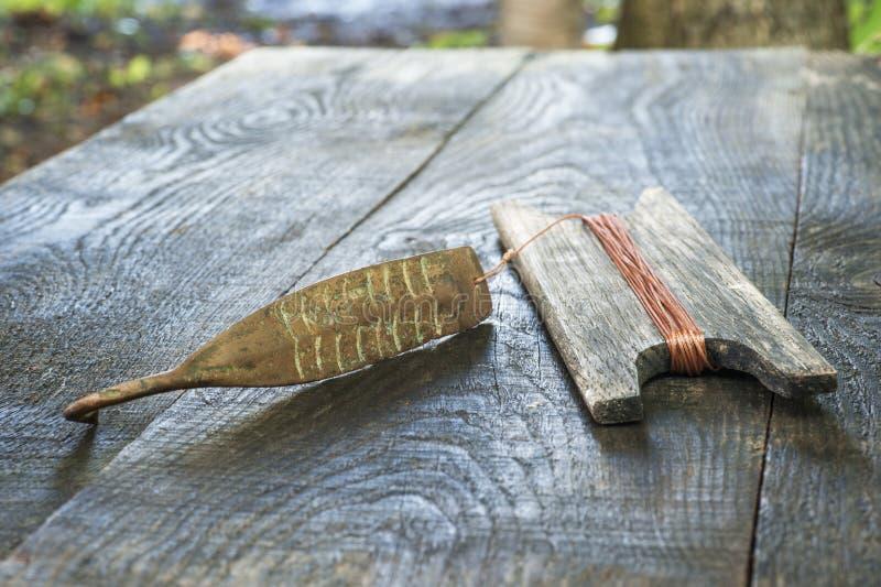 Attirail antique pour les poissons prédateurs instantané vertical Fileur et bobine forgés de cuivre avec la corde sur le fond rus photographie stock