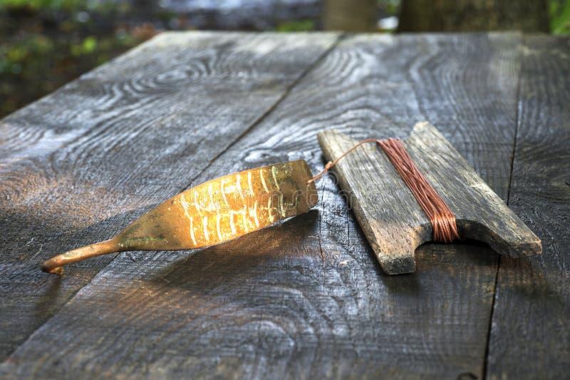 Attirail antique pour les poissons prédateurs instantané vertical Fileur et bobine forgés de cuivre avec la corde sur le fond rus photo libre de droits