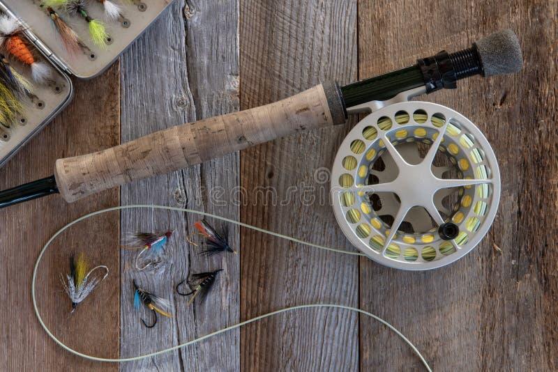 Attirails et attirail de pêche de mouche sur le bois superficiel par les agents photos stock
