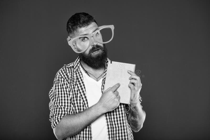 Attirer l'attention sur son manuel Ballot de livre portant les lunettes de fantaisie Homme barbu en verres de partie avec le livr photographie stock