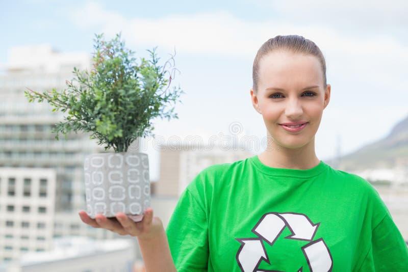 Attivista abbastanza ambientale felice che mostra una pianta fotografie stock