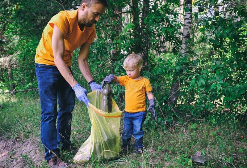 Attivisti dei volontari che prendono lettiera nel parco Padre ed suo figlio del bambino che puliscono foresta per conservare ambi immagine stock