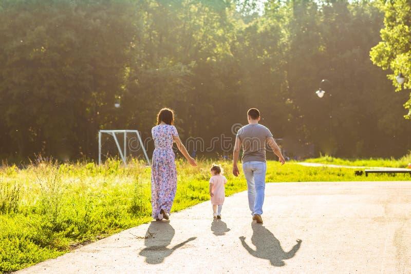 Attività all'aperto della famiglia felice Retrovisione dei genitori e della figlia del bambino divertendosi e camminando nel parc fotografia stock