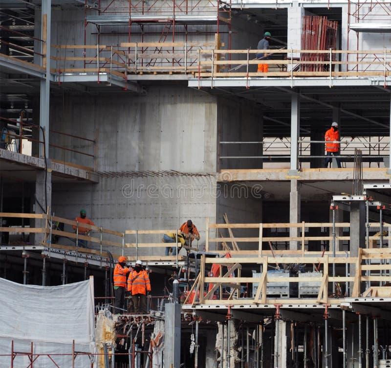 Attività del cantiere I lavoratori con lavoro dura in una costruzione nuova fotografie stock