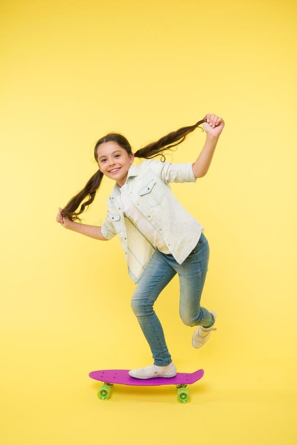 Attività del favorito di hobby Supporto sorridente del fronte del bambino sul pattino Pattino variopinto sveglio del bordo del pe immagine stock libera da diritti