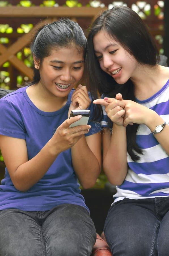 Attività delle ragazze: Per mezzo del telefono astuto immagini stock libere da diritti