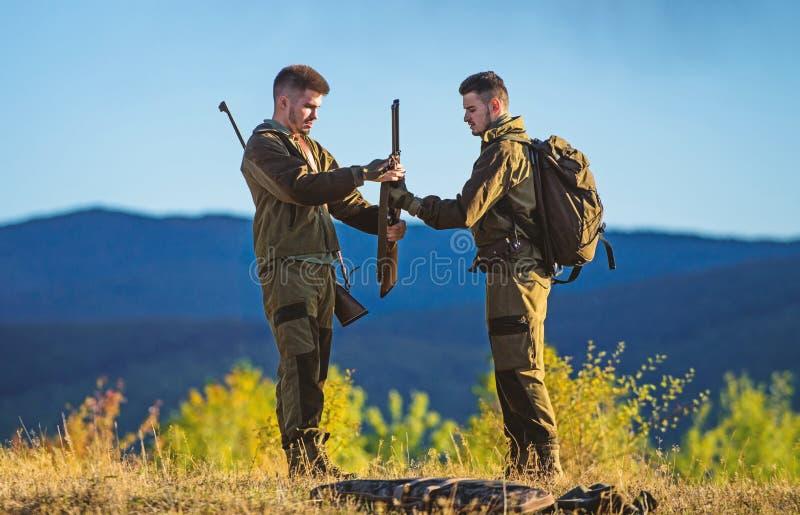 Attività maschile di hobby Cacciatori barbuti degli uomini con il fondo della natura del fucile L'esperienza e la pratica presta  fotografia stock