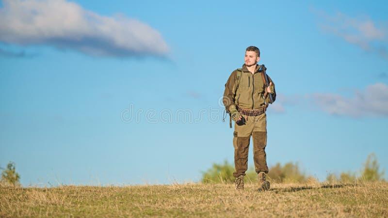Attività maschile di hobby Il cacciatore dell'uomo porta il fondo del cielo blu del fucile L'esperienza e la pratica presta la ca fotografia stock