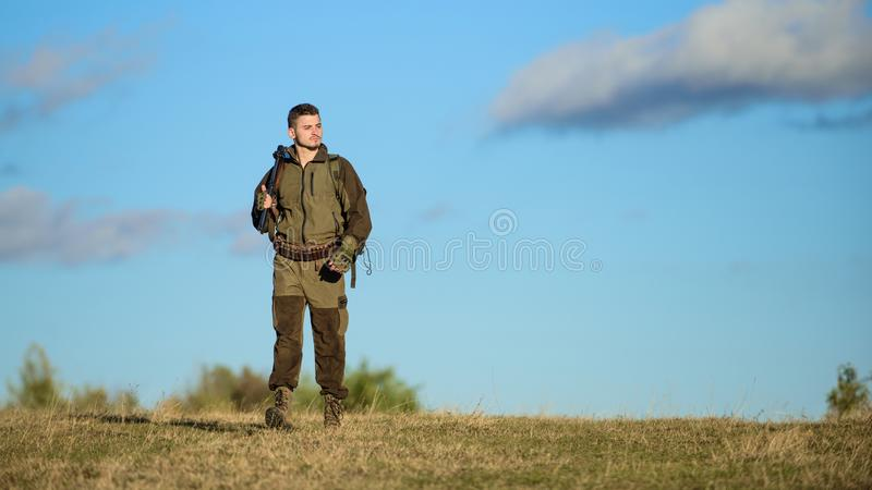 Attività maschile di hobby Il cacciatore dell'uomo porta il fondo del cielo blu del fucile L'esperienza e la pratica presta la ca fotografie stock