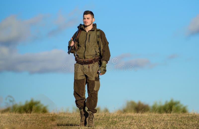 Attività maschile di hobby Il cacciatore dell'uomo porta il fondo del cielo blu del fucile L'esperienza e la pratica presta la ca immagini stock