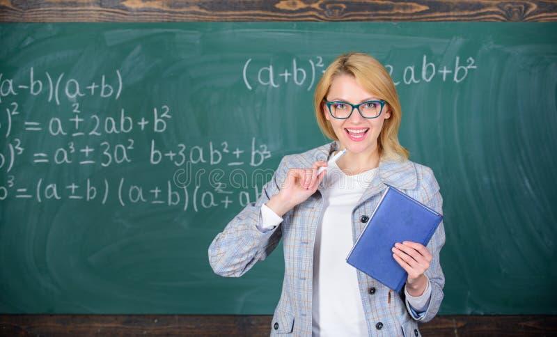 Attivit? complessa complessa d'istruzione La donna astuta dell'insegnante con il libro spiega l'argomento vicino alla lavagna Che fotografia stock
