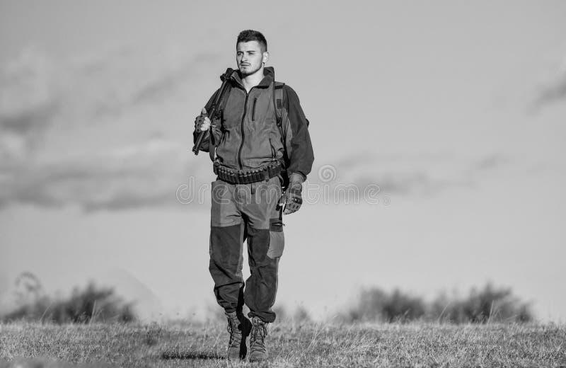 Attivit? maschile di hobby Il cacciatore dell'uomo porta il fondo del cielo blu del fucile L'esperienza e la pratica presta la ca fotografie stock libere da diritti
