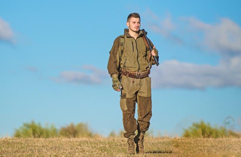 Attivit? maschile di hobby Il cacciatore dell'uomo porta il fondo del cielo blu del fucile L'esperienza e la pratica presta la ca immagini stock