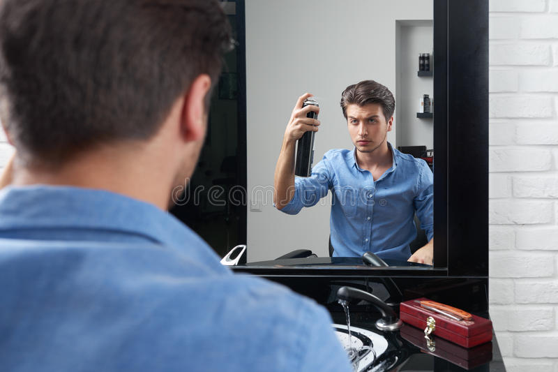 Attntive man is making hairdo and pulverize spray. Man is pulverize hairspray for hair and making hairdo stock photos