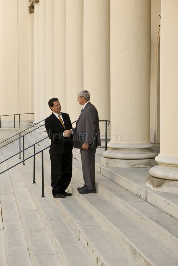 Attorney and Client. Two men shaking hands on courthouse steps