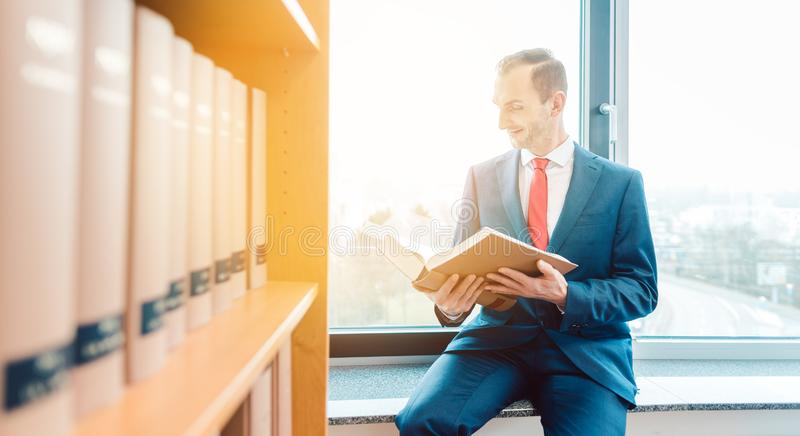 Attorney at law in the library of his office reading and thinking royalty free stock photography